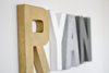 Ryan airplane nursery letters in gold, white, and grays.