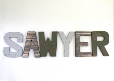 Boy's name wall nursery letters in gray, green, and brown spelling out the name SAWYER.