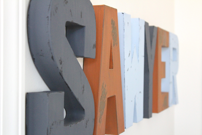Sawyer name letters for nursery wall decor in gray, orange, and light blue.