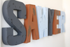 Sawyer custom wall letters in distressed grey, orange, and blue colors.