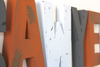 Distressed nursery letters in three different colors: orange, grey, and light blue.