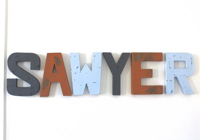 Baby letters for room decor spelling out Sawyer in three different colors: orange, grey, and blue.