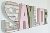 Girl nursery name sign spelling out Saylor in pink and gray.