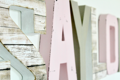 Girls room name letters spelling out the name Saylor in pink, white, and gray wall letters.