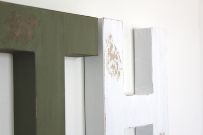 Distressed green faux wooden letters and white distressed letter H.