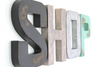 Industrial chic wall letters spelling out SHOP in black, rose gold, silver, and patina green.