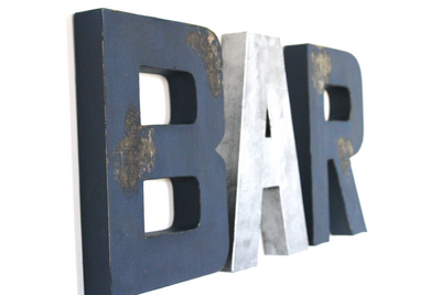 "Bar wall sign in navy distressed ""wooden"" letters and silver ""metal"" letters."