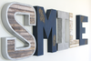 Customized letters spelling out the word SMILE in different styles and colors such as navy, silver, white, and brown.