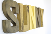 Yellow nursery decor name letters spelling out Sunny in different shades of yellow and gold.
