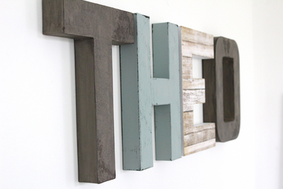 Little boys room letters spelling out Theo in grey, blue, and white.