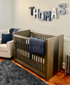 Navy and silver boy room name sign spelling out the name Thomas in navy, silver, and gray letters.