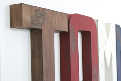 Distressed letters in brown, red, and white.