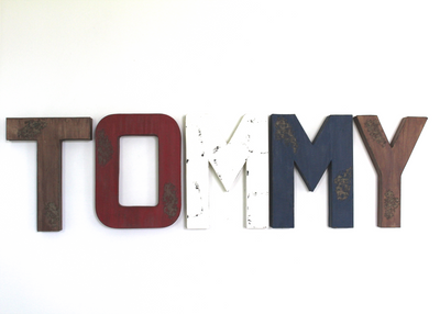 Tommy name letters in brown, red, white, and navy for rustic baby boy nursery decor.