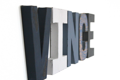 Little  boy room letters spelling out Vince in different shades of blue and grey.
