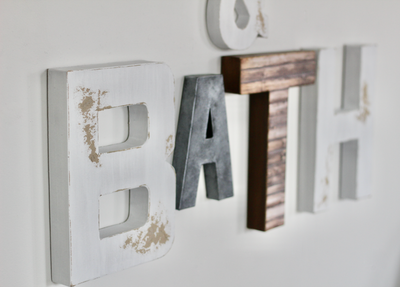 Farmhouse bath letters in white, grey, and brown letters.
