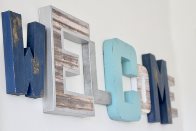 Entryway wall decor welcome sign done in different styles and colors.