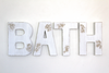 Bath wall sign in distressed white farmhouse letters.