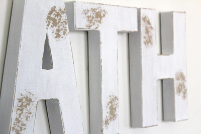Distressed white wall letters in a rustic farmhouse style.