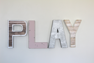 Play sign for girl's playroom wall decor with a pink letter L.