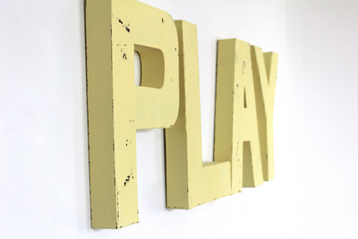 "Playroom ""wooden"" wall sign in yellow."