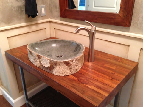 An andesite stone vessel sink in a powder bathroom installed on a custom teak and steel vanity from Impact imports in Boise Idaho.