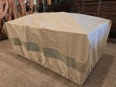 A rectangular shaped IMPACT Fire Table with a khaki colored polyester cover.
