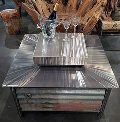 A square IMPACT Fire Table with a hand brushed stainless steel firebox cover installed