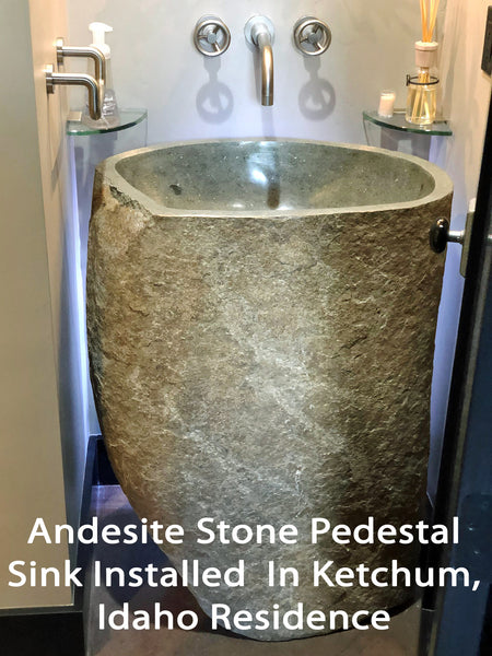 Installation view of an Andesite Stone Pedestal Sink hand cut from a single piece of basalt stone with a polished bowl and lip and naturally organic exterior.