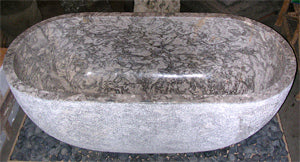 Custom marble bathtub cut and hand made from a single piece of gray marble with a polished bowl and top lip and a hand chiseled exterior for a modern rustic look
