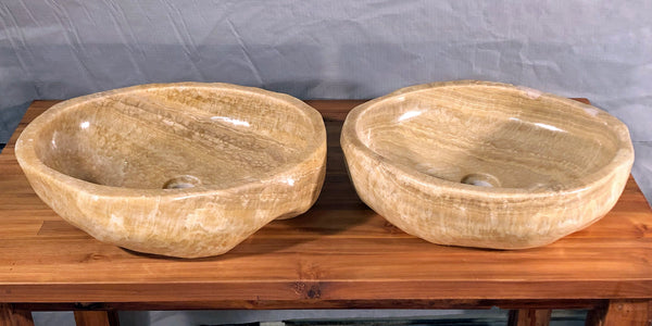 A pair of organically shaped dark honey or root beer float brown onyx vessel bathroom sink hand cut from a single stone rock and polished at Impact Imports Boise Idaho.