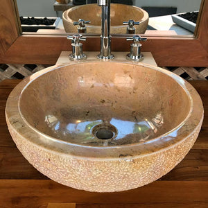 A reddish colored marble round bowl vessel sink with a polished bowl and lip and a hand chiseled exterior for a traditional modern rustic style look