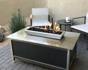 A modern industrial style, heavy duty stainless steel rectangular shaped IMPACT propane or natural gas burning Fire Table or fire pit for entertaining or relaxing outdoors on your patio, rooftop deck or in your garden.  Made in America USA.