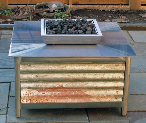 A modern industrial rustic farmhouse style, heavy duty stainless steel Square shaped IMPACT propane or natural gas burning Fire Table or fire pit with salvaged corrugated steel exterior side panels for entertaining or relaxing outdoors on your patio, rooftop deck or in your garden.  Made in America USA.