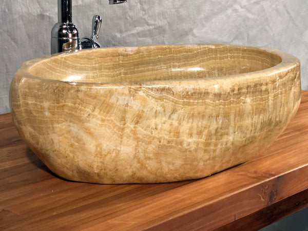 An organically shaped dark honey or root beer float brown onyx vessel bathroom sink hand cut from a single stone rock and polished at Impact Imports Boise Idaho.