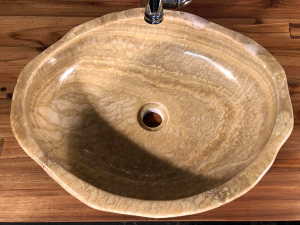 Top view of an organically shaped dark honey or root beer float brown onyx vessel bathroom sink hand cut from a single stone rock and polished at Impact Imports Boise Idaho.