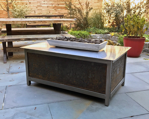 A modern industrial style, heavy duty hand brushed stainless steel rectangular shaped IMPACT propane or natural gas burning Fire Table or fire pit with salvaged raw steel exterior side panels for entertaining or relaxing outdoors on your patio, rooftop deck or in your garden.  Made in the USA America