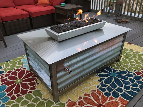 A modern industrial rustic farmhouse style, heavy duty stainless steel rectangular shaped IMPACT propane or natural gas burning Fire Table or fire pit with salvaged corrugated steel exterior side panels for entertaining or relaxing outdoors on your patio, rooftop deck or in your garden.  Made in America USA.