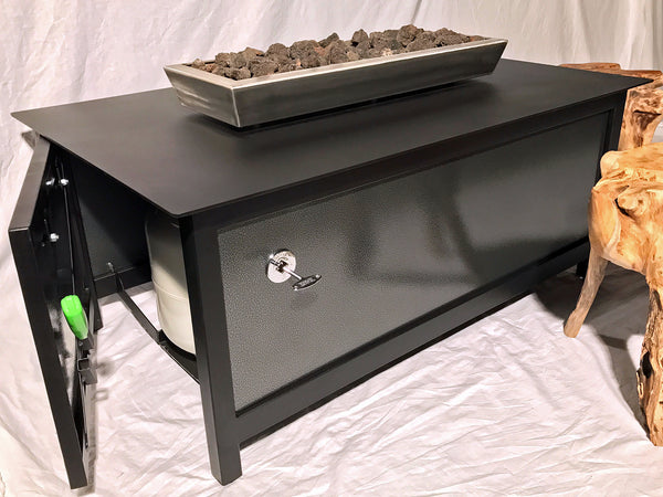 A view of the open access door, the hidden propane tank and the holster on a heavy duty, high quality rectangular shaped outdoor steel fire table with raven black frame and table top and silver vein powder coated steel side panels for burning propane or natural gas.  Made in the USA America.