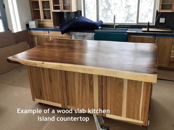 Picture of a natural live edge wood slab kitchen island countertop with a satin urethane finish installed in a home in Donnelly Idaho