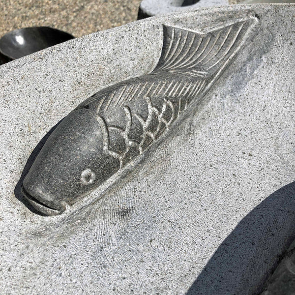 Detail picture of the carved koi fish in the bowl of a River boulder rock bird bath with Koi Fish motif.  Bowl is hand cut from a single piece of natural stone.