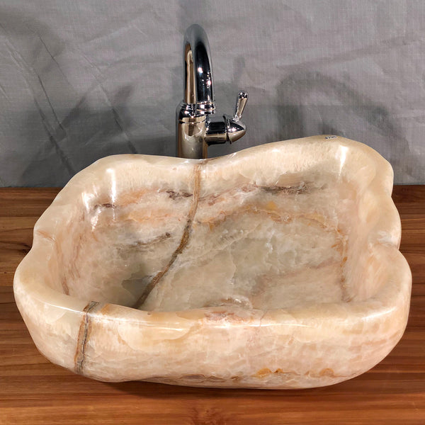 An organically shaped vessel sink hand made from a single piece of mixed honey onyx colored stone available at Impact Imports in Boise Idaho
