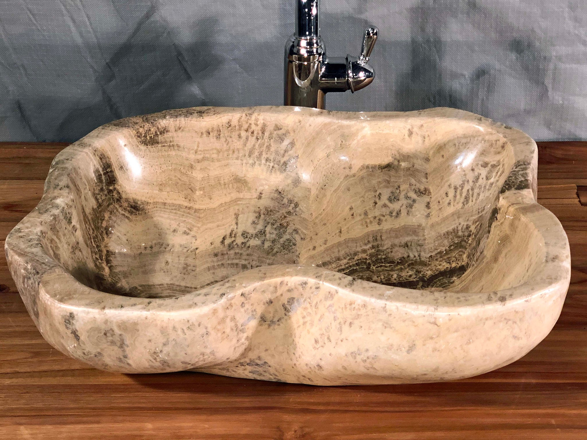 A large mixed marble and onyx vessel sink hand made from a single piece of brown and cream colored stone available at Impact Imports in Boise Idaho.