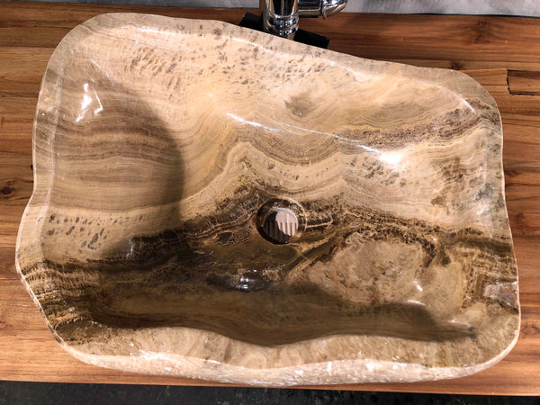 A mixed marble and onyx vessel sink hand made from a single piece of brown and cream colored stone available at Impact Imports in Boise Idaho.