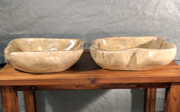 A pair of large mixed marble and onyx vessel sinks hand made from single pieces of brown and cream colored stone available at Impact Imports in Boise Idaho.