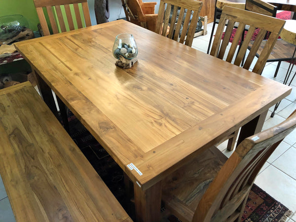 A 5 foot long by 3 foot wide dining table with a sold 1 and 5 8ths inch thick table top made from reclaimed teak wood.