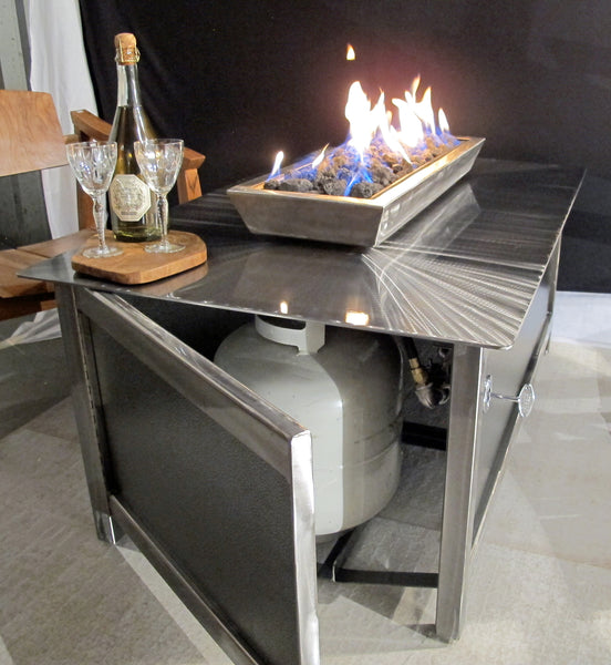 The access door and propane tank of A modern industrial style, heavy duty stainless steel rectangular shaped IMPACT propane or natural gas burning Fire Table or fire pit for entertaining or relaxing outdoors on your patio, rooftop deck or in your garden.  Made in America USA.