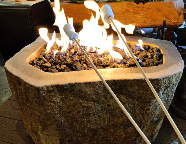 Roasting marshmallows over an Andesite natural stone gas fire pit hand carved from real rock for burning natural gas or propane