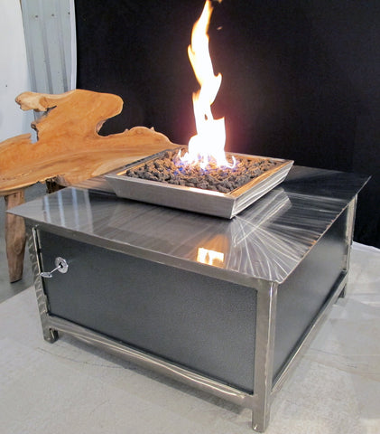 A modern industrial style, heavy duty stainless steel square shaped IMPACT propane or natural gas burning Fire Table or fire pit for entertaining or relaxing outdoors on your patio, rooftop deck or in your garden.  Made in America USA.