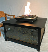 An edgy, urban, contemporary, modern industrial rustic farmhouse style, heavy duty steel Square shaped IMPACT propane or natural gas burning Fire Table or fire pit with salvaged raw steel exterior side panels and a raven black powder coated frame and table top for entertaining or relaxing outdoors on your patio, rooftop deck or in your garden.  Made in America USA.