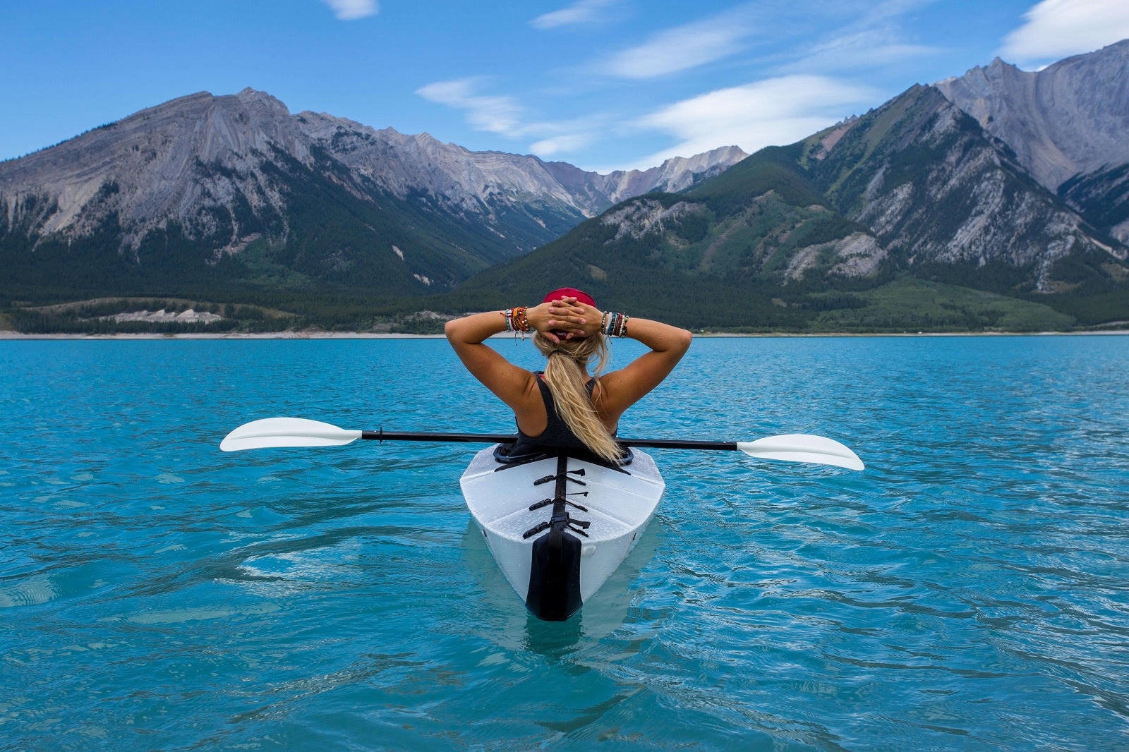 girl in white kayak on blue water with mountains in the distance
